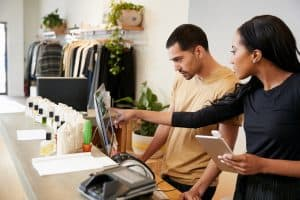 man and woman working behind retail counter